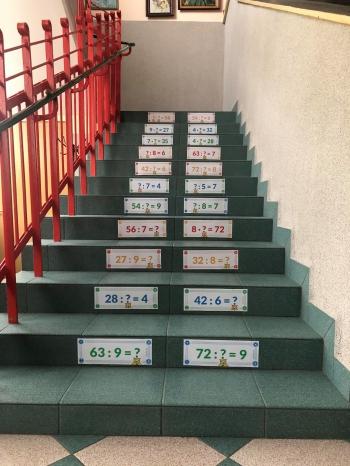 Naklejki z tabliczką mnożenia na stopniach schodów w szkole