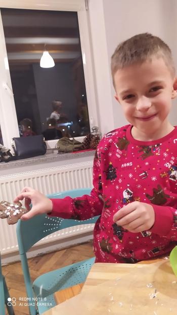 dziecko dekoruje świąteczne wypieki