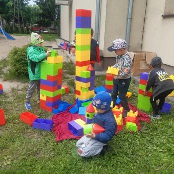 pięciu chłopców buduje wieże z dużych kolorowych klocków  rozłożonych na placu zabaw