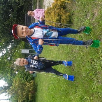 dwóch chłopców chodzi na szczudłach. W tle jedna dziewczynka przygląda się innym dzieciom.