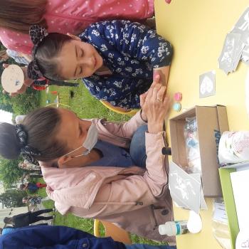 przy stoliku siedzi uśmiechnięta  dziewczynka oraz dorosła kobieta wykonująca na rączce dziewczynki kolorowy, brokatowy tatuaż. W tle bawiące się dzieci