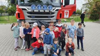 kilkunastoosobowa  grupa dzieci stoi przed wozem strażackim