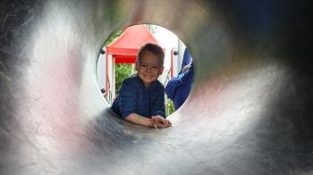 chłopczyk w tunelu na przedszkolnym placu zabaw