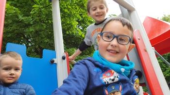 trzech chłopców bawi się na przedszkolnym placu zabaw