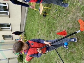 Jeden chłopiec pokonuje tor przeszkód  tocząc slalomem  pomiędzy pachołkami piłeczkę za pomocą kija do hokeja.