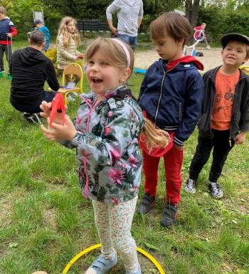 uśmiechnięta  dziewczynka stoi w kole( linii startu), trzyma w ręku materiałową rzutkę, celuje nią w tarczę. Za nią stoi dwóch chłopców w oczekiwaniu na swoją kolej. W tle grupa dzieci bawi się na placu zabaw.