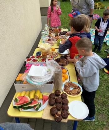 kilkuosobowa grupa dzieci stoi przy stole ustawionym na dworze, na którym znajdują się przekąski, owoce, słodycze i napoje. Dzieci częstują się smakołykami.