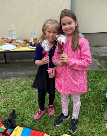 dwie dziewczynki w wieku przedszkolnym stoją na dworze na tle stołu z przekąskami pozując do zdjęcia uśmiechnięte z  kolorowymi bezowymi lizakami w rękach.