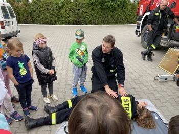 grupa dzieci w wieku przedszkolnym stoi ustawiona w półkolu wokół strażaka prezentującego im sposób udzielania pierwszej pomocy poszkodowanemu