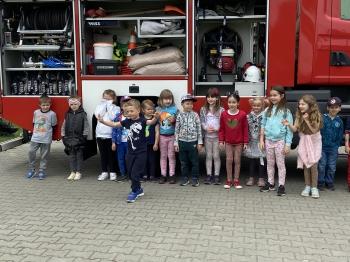 kilkunastoosobowa  grupa dzieci w  wieku przedszkolnym ( chłopców i dziewczynek) stoi przed wozem strażackim pozując do grupowego zdjęcia