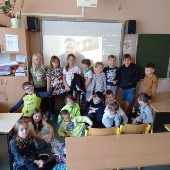 Kilkunastoosobowa grupa dzieci w wieku szkolnym pozuje do zdjęcia na tle tablicy multimedialnej.
