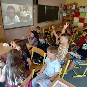 Kilkunastoosobowa grupa dzieci w wieku szkolnym pozuje do zdjęcia