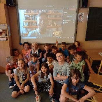 Kilkunastoosobowa grupa dzieci w wieku szkolnym pozuje do zdjęcia na tle tablicy multimedialnej
